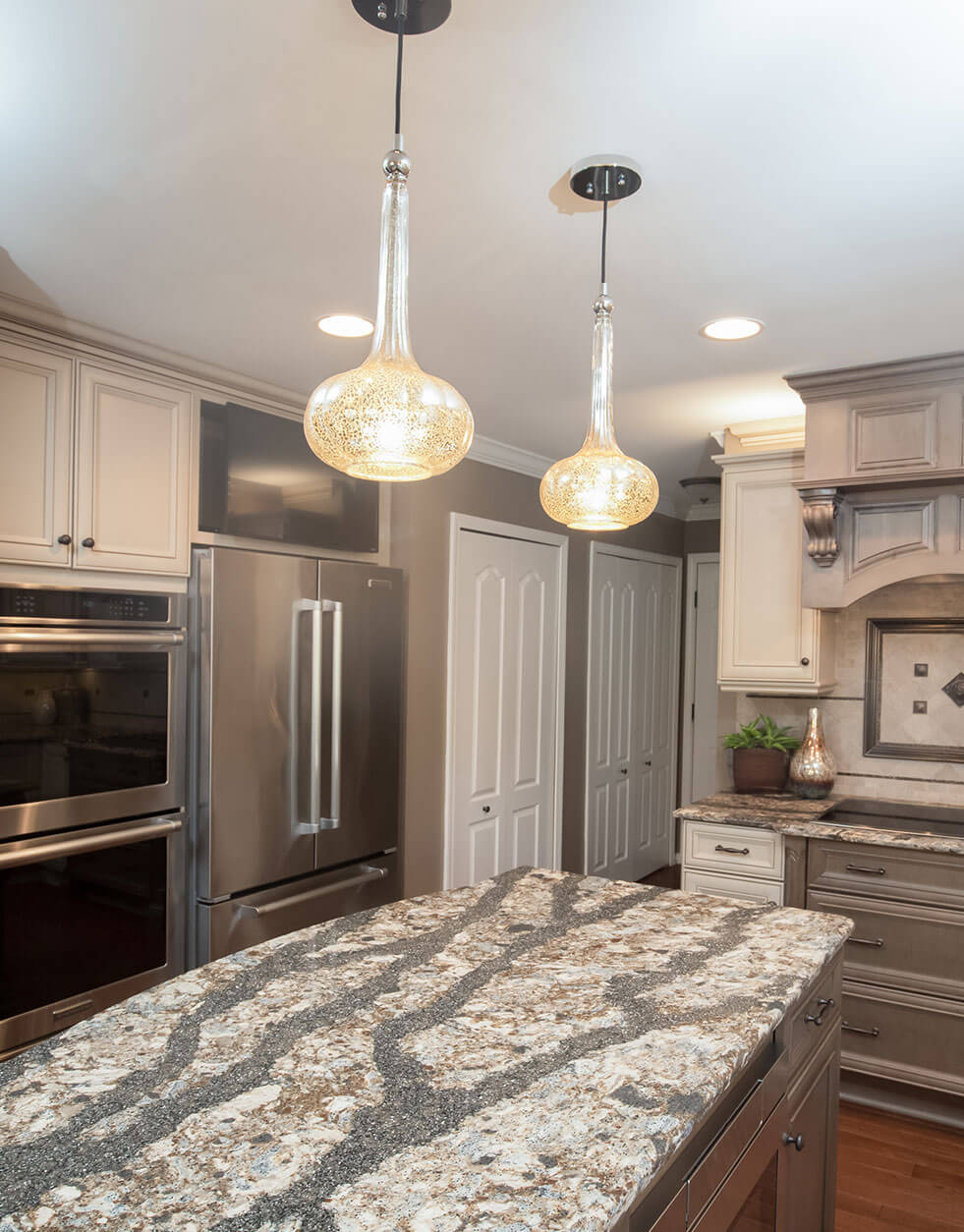 Unique white granite kitchen countertop with streaks of dark gray, lit from above with 2 contemporary glass lighting fixtures.