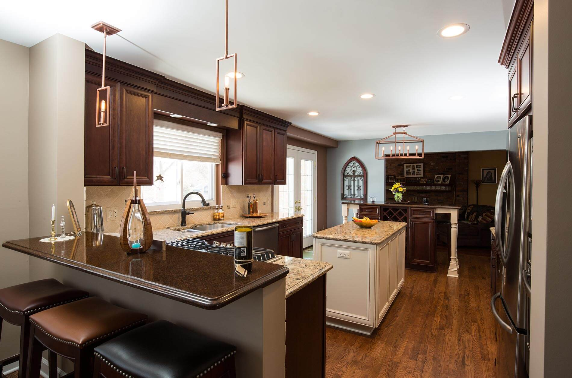 Kitchen with dark stained cabinets, white center work island and separate snack bar.