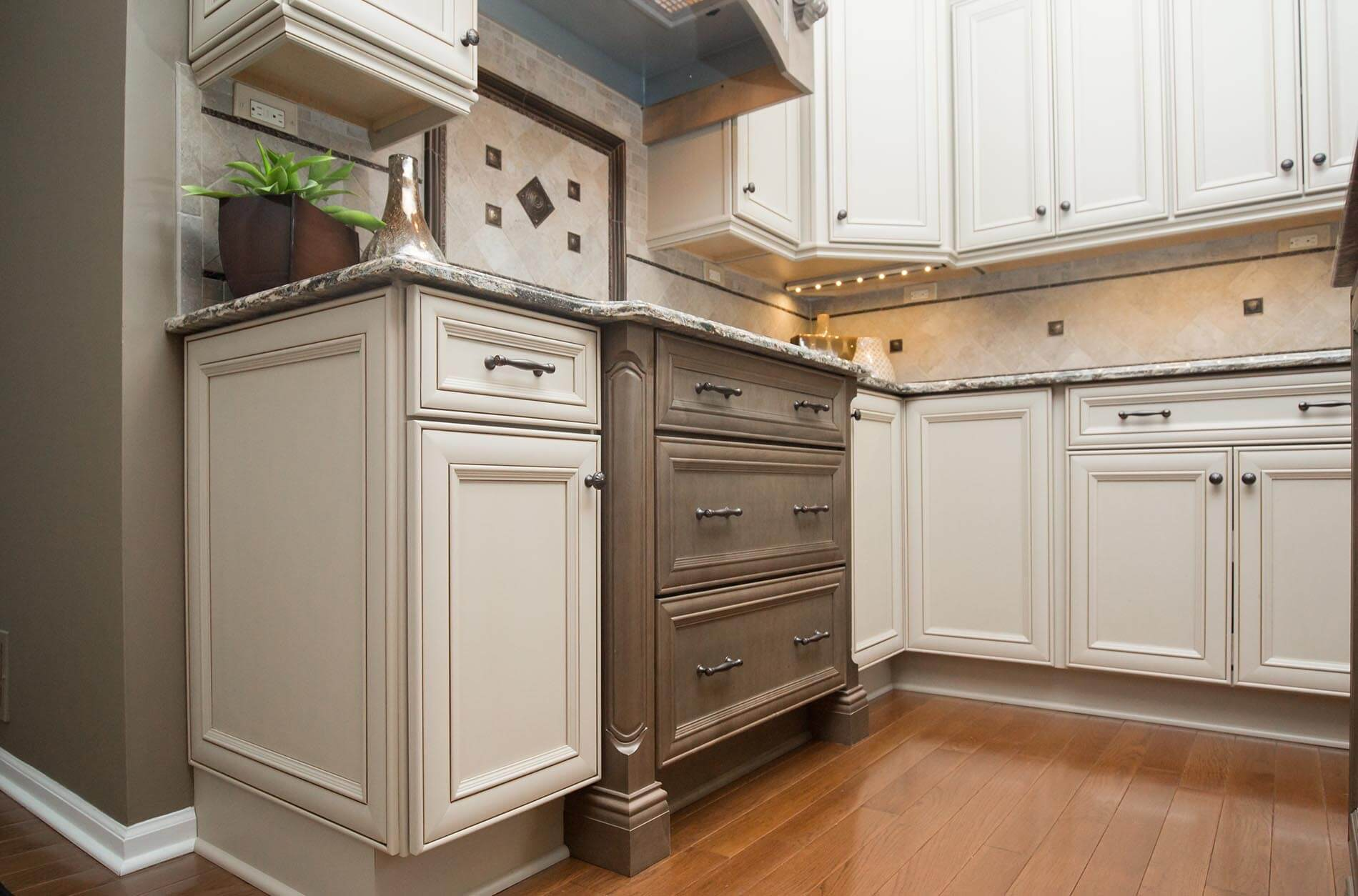 Two-toned kitchen cabinets in off-white and soft gray, including a dresser-style cabinet below the drop-in cooktop.